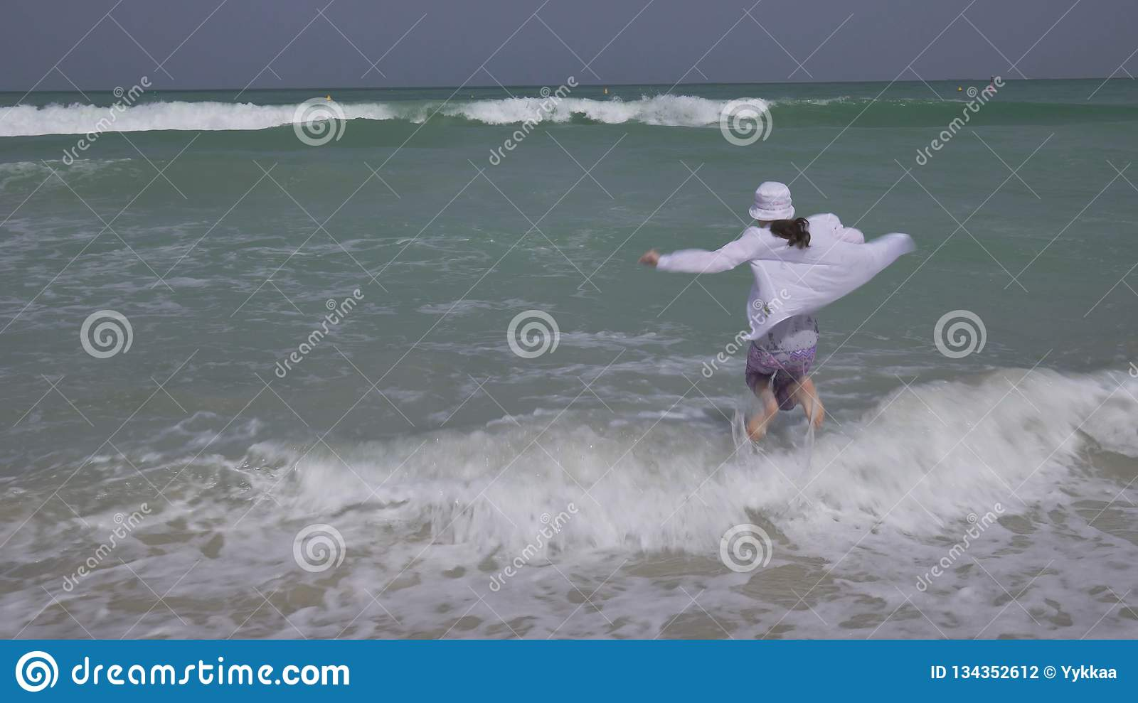 Teenage Girl In Clothes Joyfully Jumping In The Waves Of