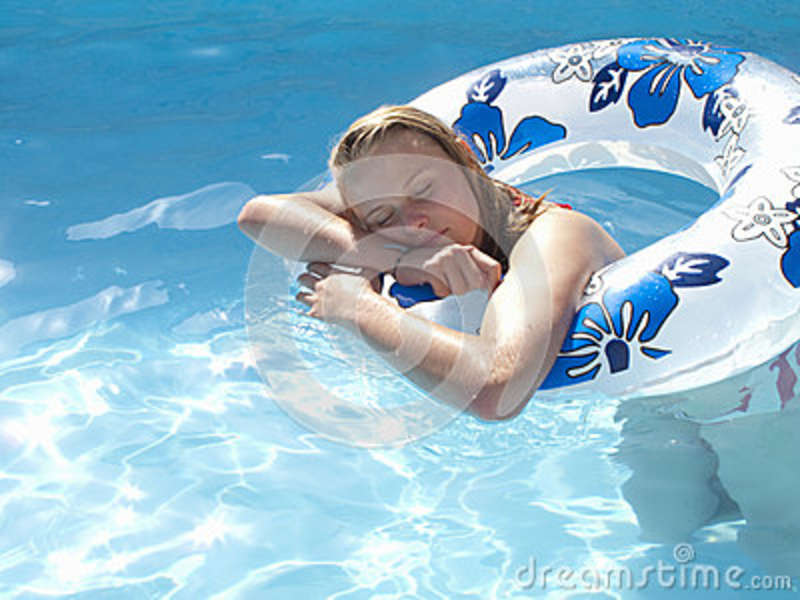 Teenage girl with eyes closed leaning on inflatable ring in swimming pool