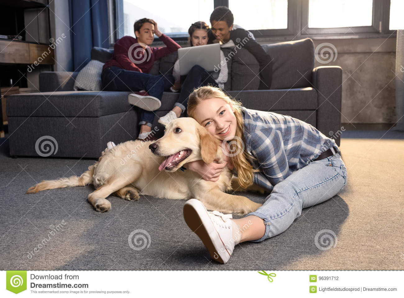 Teenage Girl Having Fun With Golden Retriever Dog While Friends