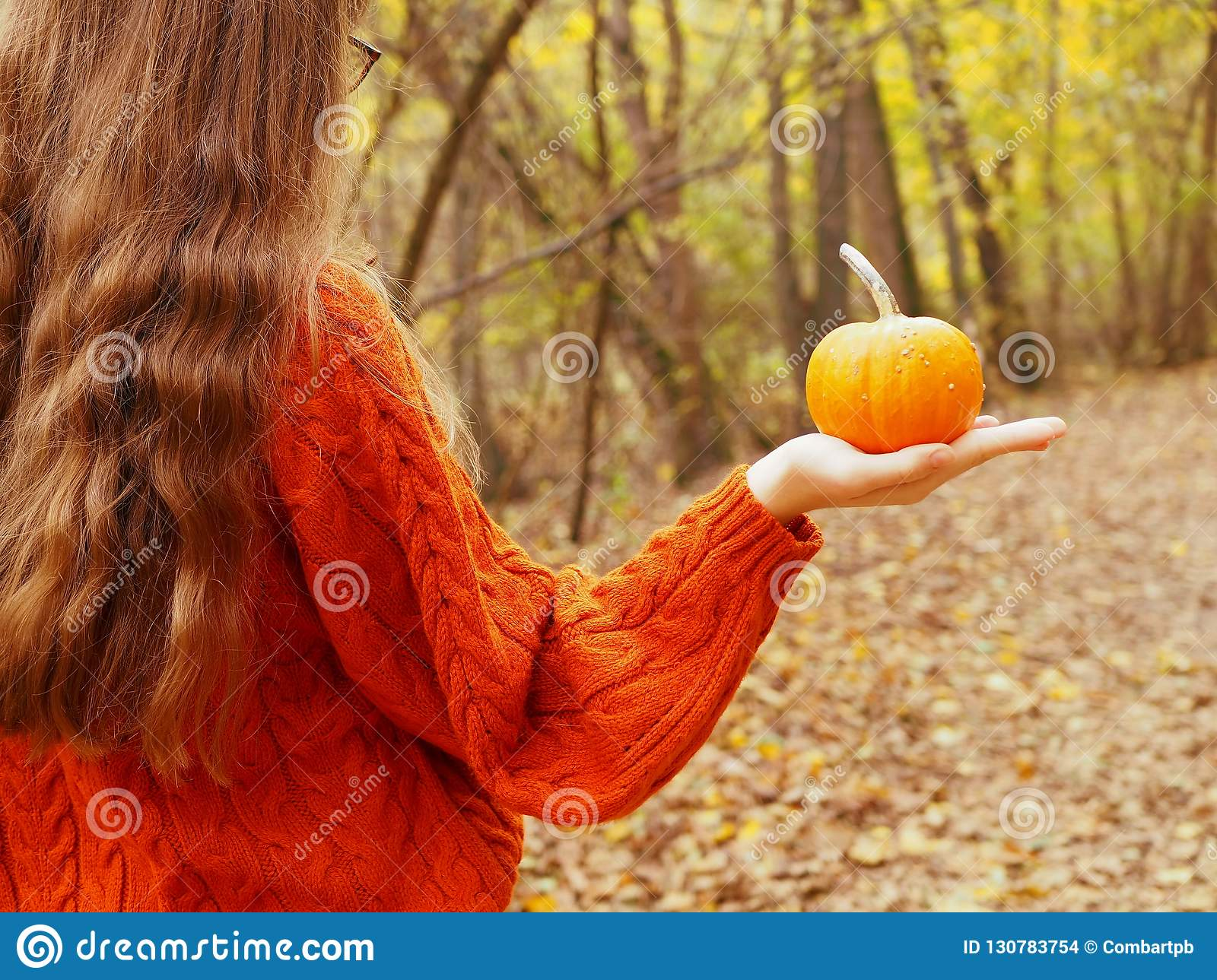 A teenage girl holding a pumpkin in her hand walking in the forest