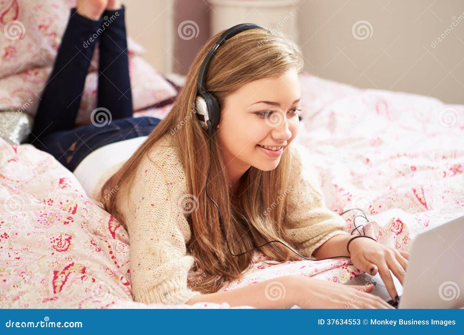 Teenage Girl Lying On Bed Using Laptop Wearing Headphones