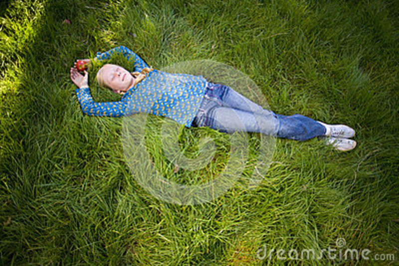 Teenage girl (11-13) lying in grass with eyes closed, elevated view (full frame)