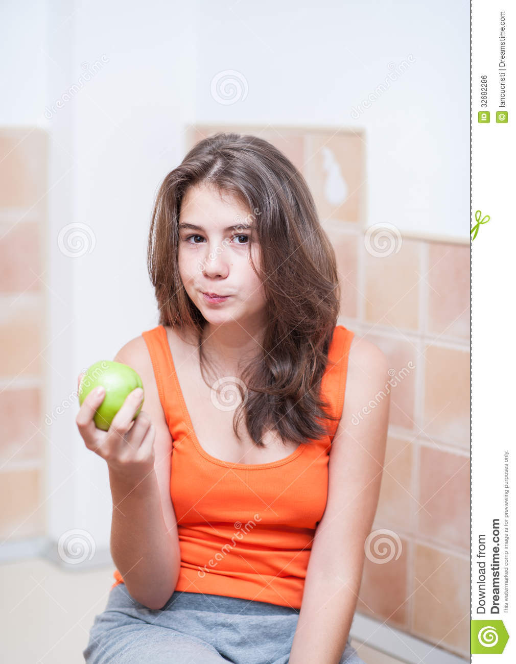 Beautiful and young teenage girl in orange t-shirt eating with joy a green  apple
