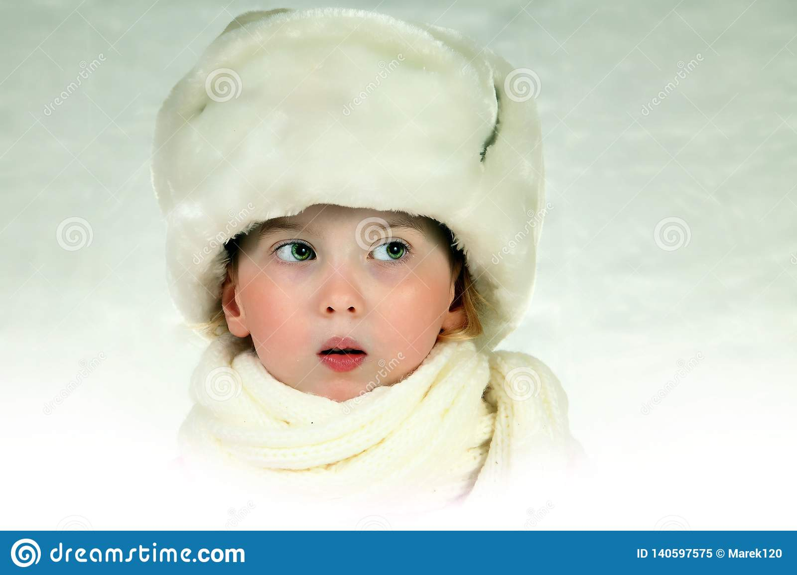 Teenage girl posing as frozen in cold. White furry hat - atmosphere of cold winter