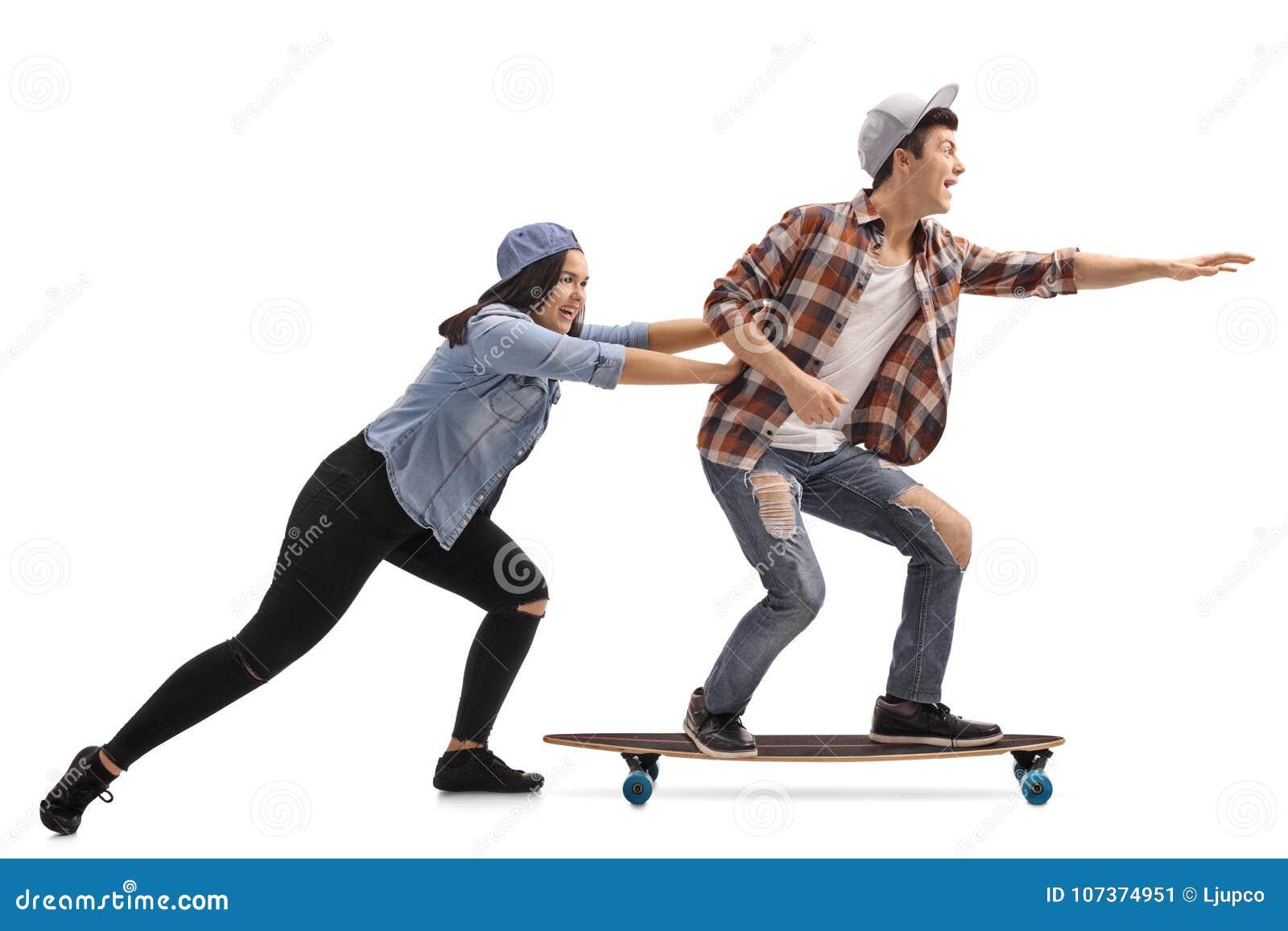 Teenage girl pushing a teenage boy on a longboard