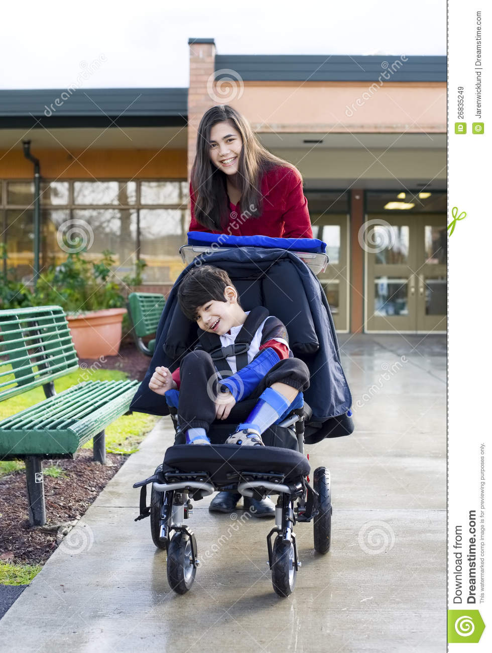 Teenage Girl Pushing Disabled Boy In Wheelchair Royalty