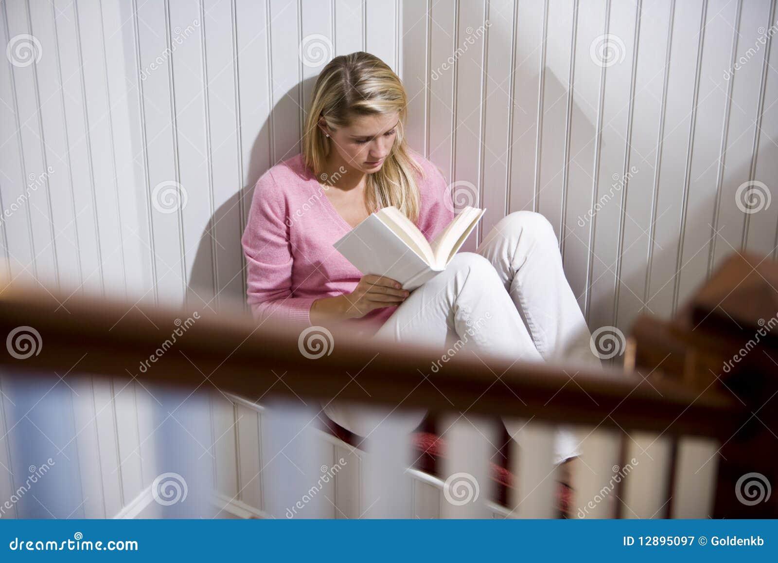 Teenage girl reading alone in quiet corner