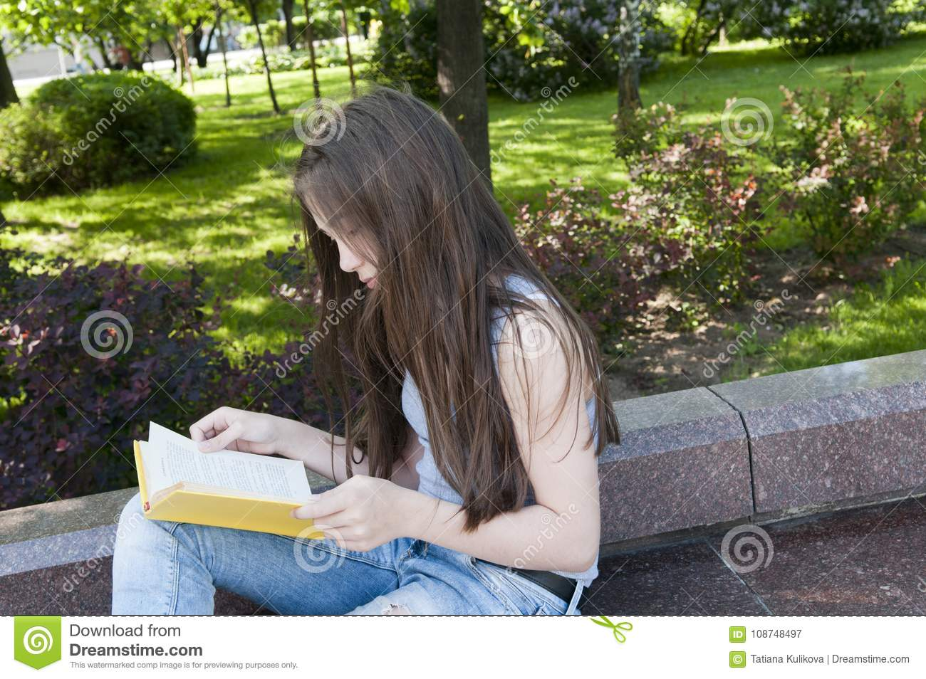 Cute Teenage Girl Reading Book Sitting On The Bench In
