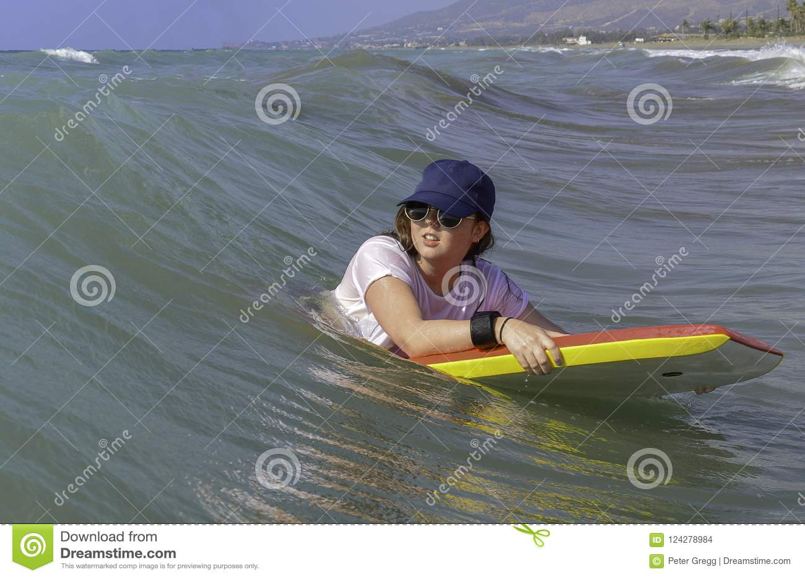 Teenage girl on red and Yellow bodyboard