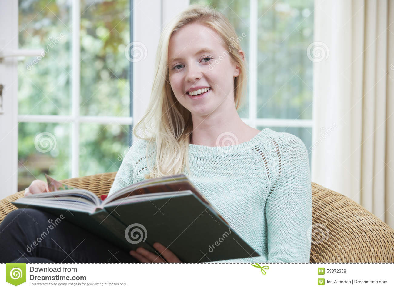 Teenage Girl Relaxing And Reading Book At Home