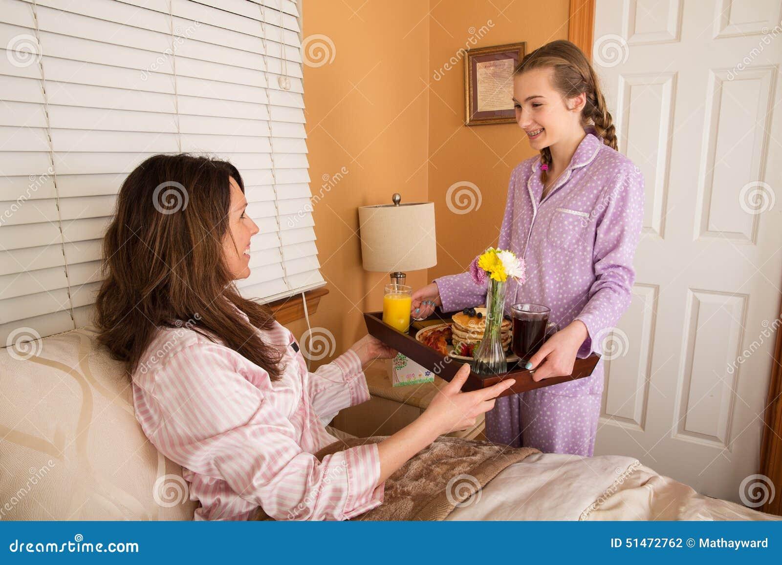teenage girl serving mom breakfast in bed stock photo - image