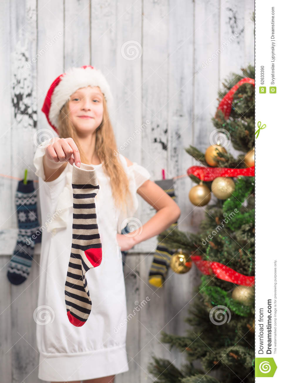 Teenage girl showing New Year and Christmas sock to the photographer.  Pretty lady demonstrating empty stripped sock.