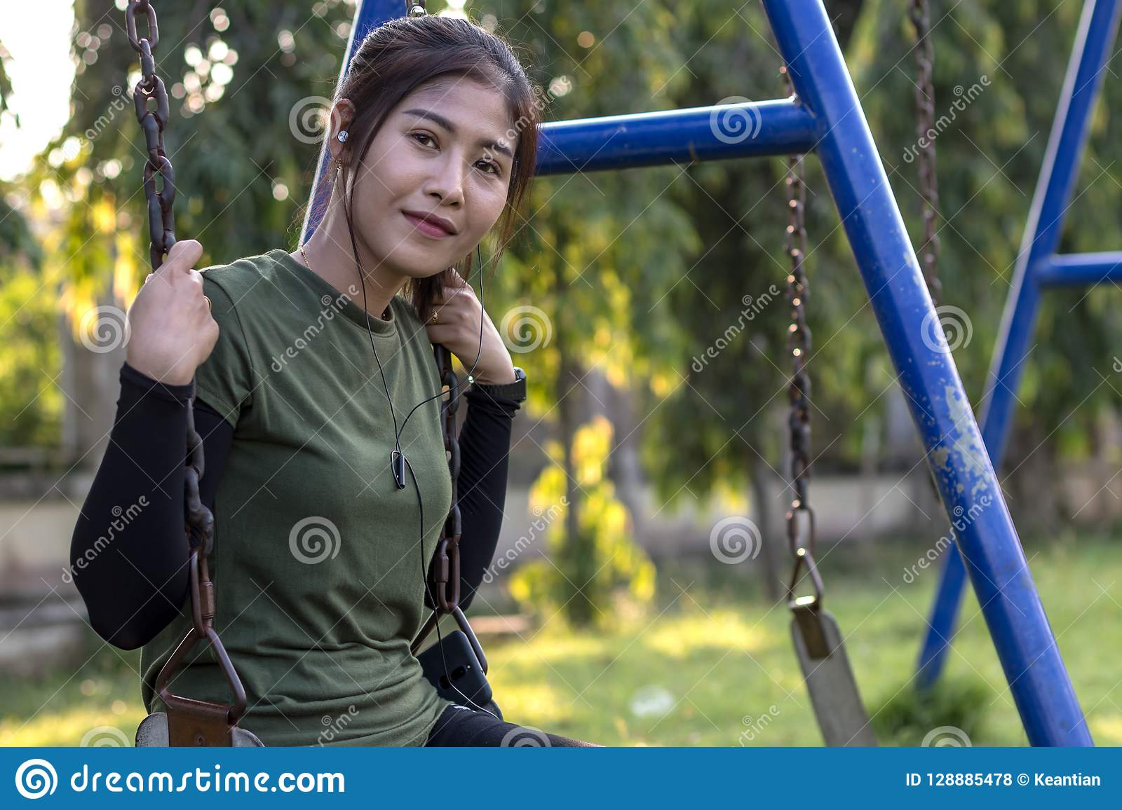 Teenage girl sitting on a swing chain smiling.