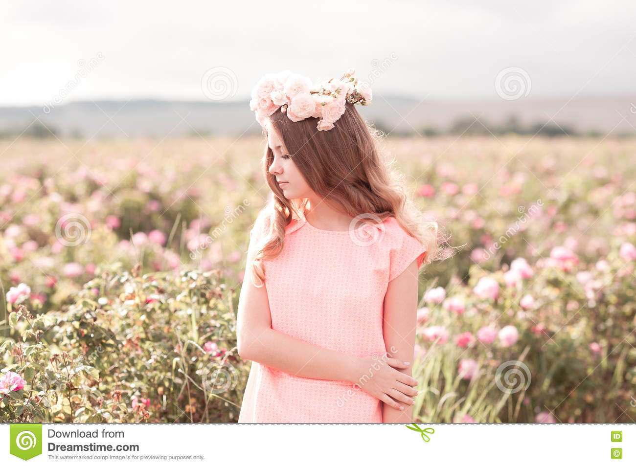 Teenage girl standing in rose garden
