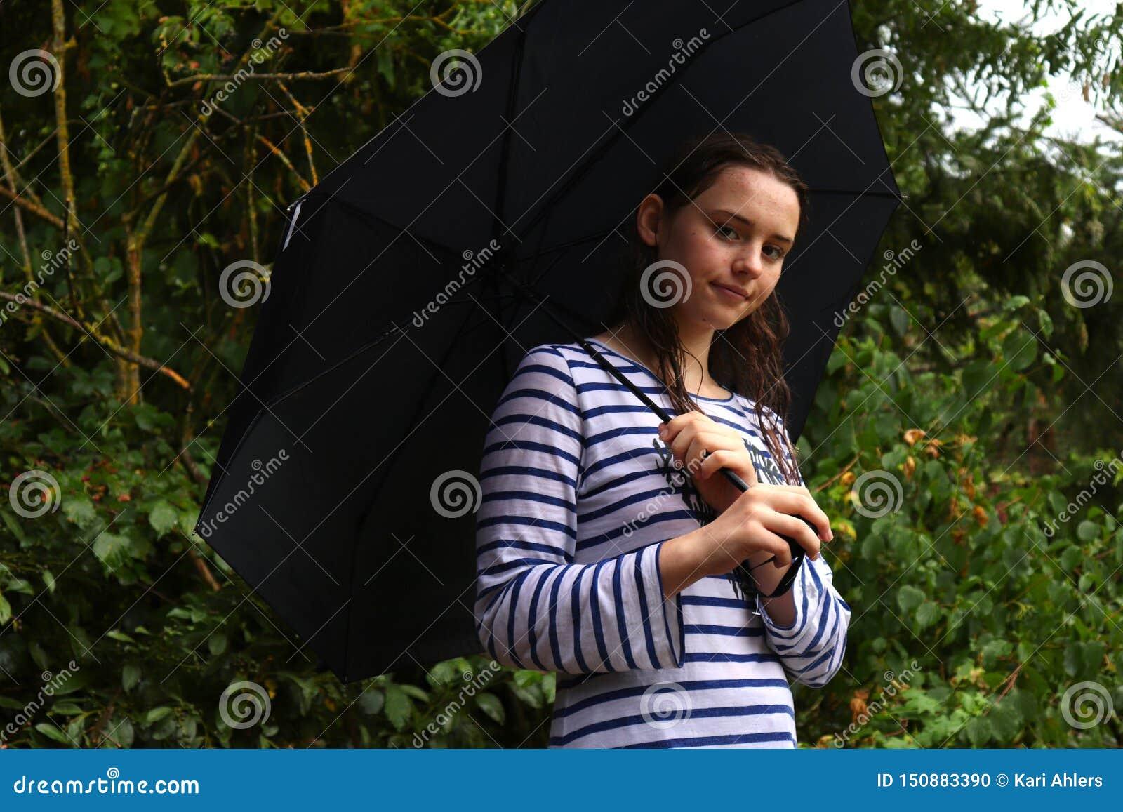 Teenage girl standing under an umbrella in the rain