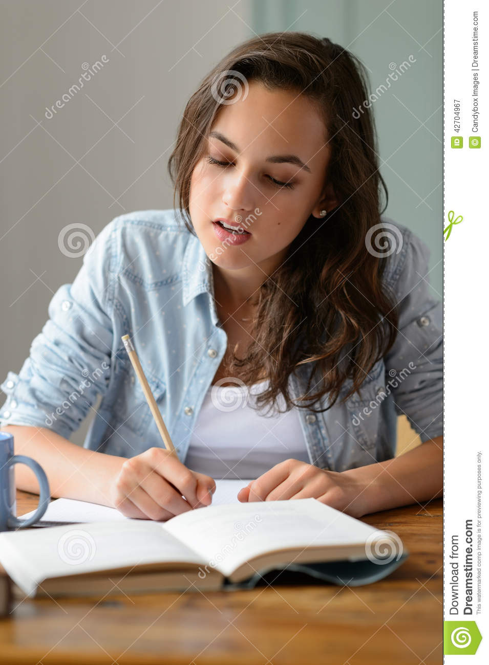 Teenage girl studying book writing notes