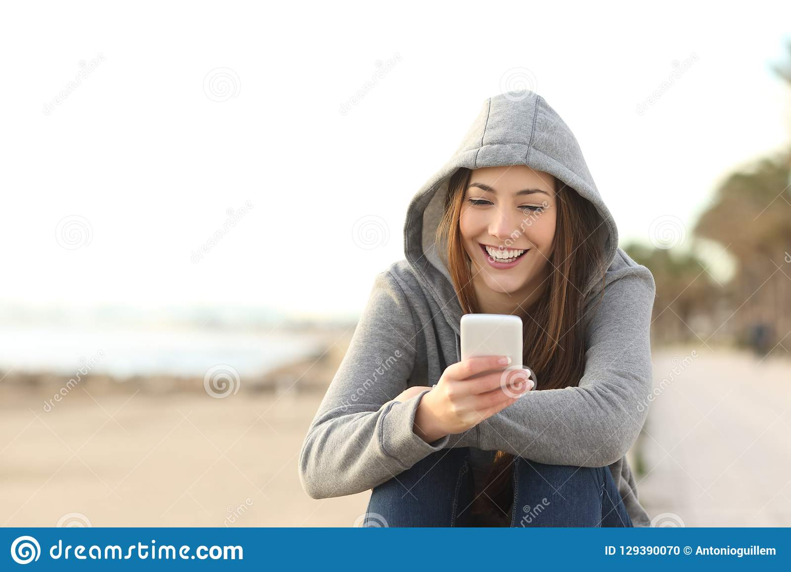 Teenage girl using a smart phone on the beach