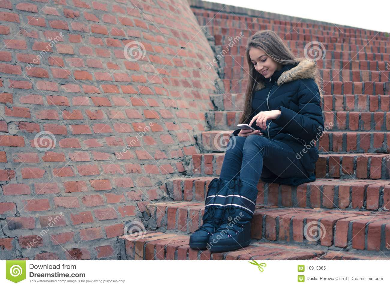 Teenage girl using smartphone sitting by brick wall