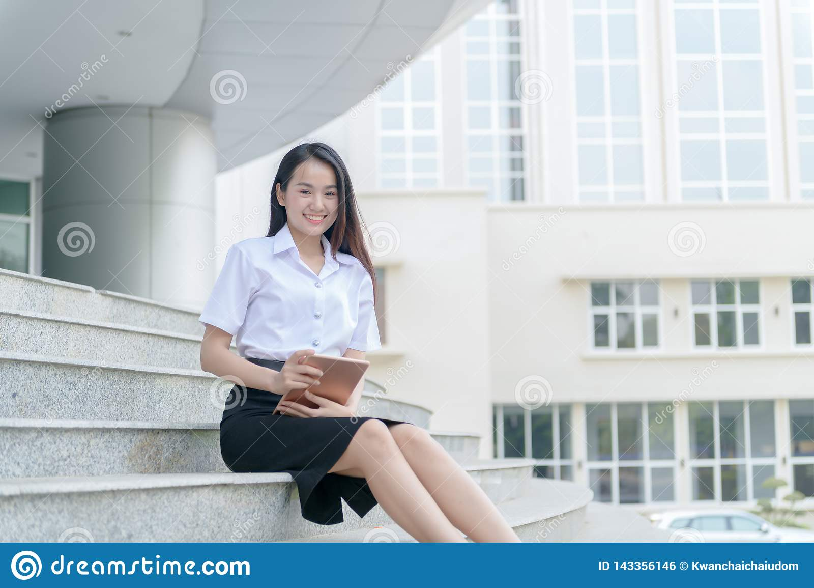 Teenage girl wearing uniform and using tablet
