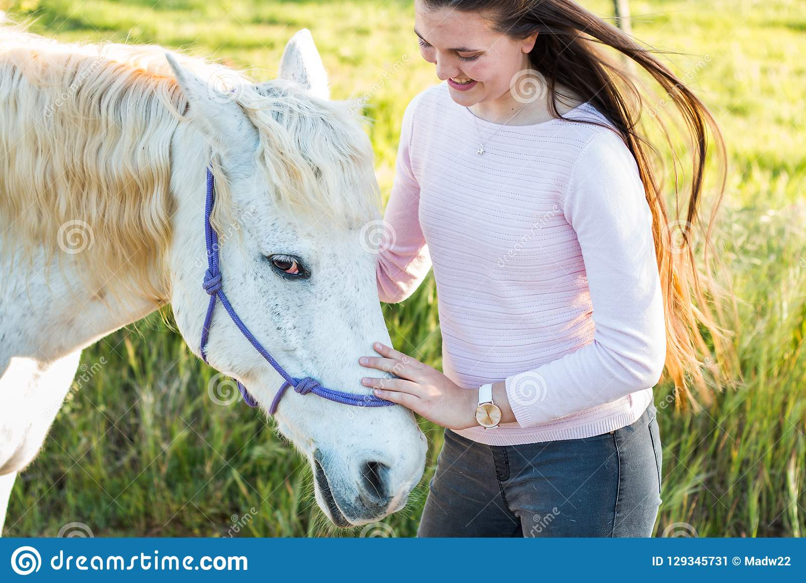 Teenage girl with a white Boerperd horse standing by his head petting his nose