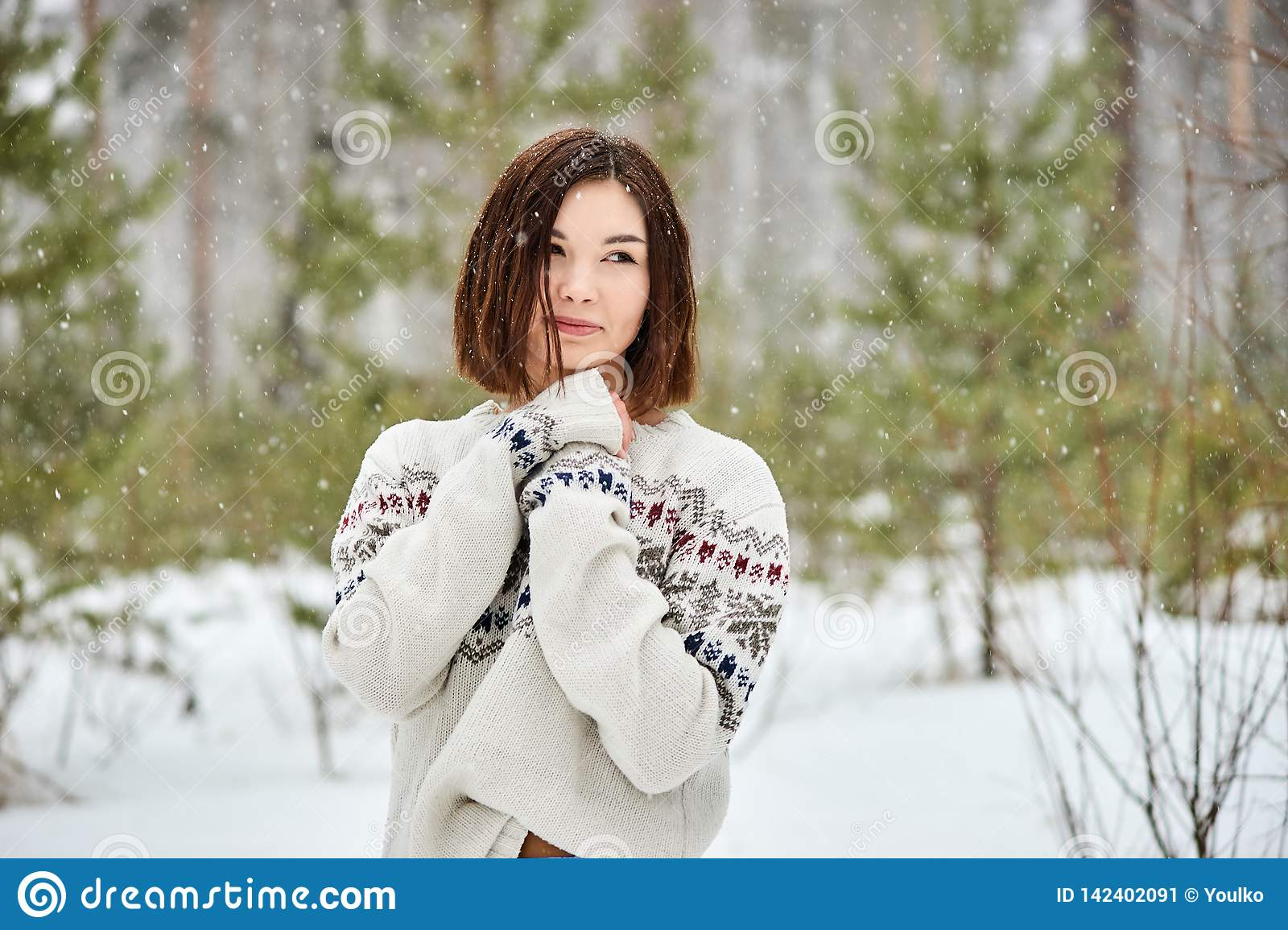Teenage girl in the winter forest. Snowfall