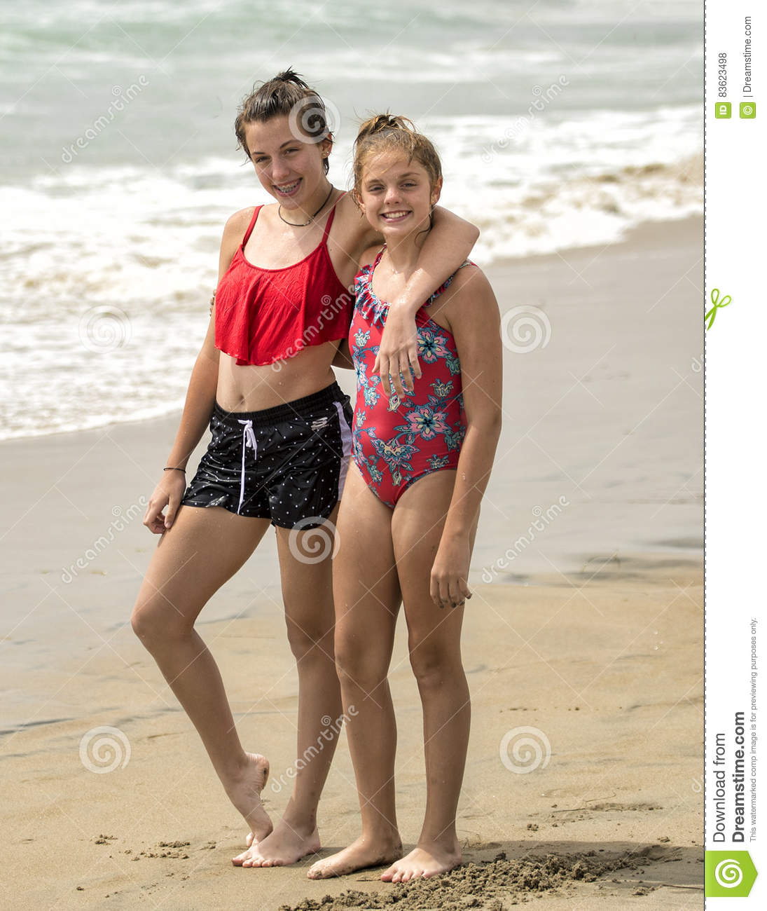 ea9a995f34c6c Two teenage sisters standing in the sand on Mission Beach in California.  The fifteen year old is wearing a two-piece swimsuit and has her left arm  draped ...