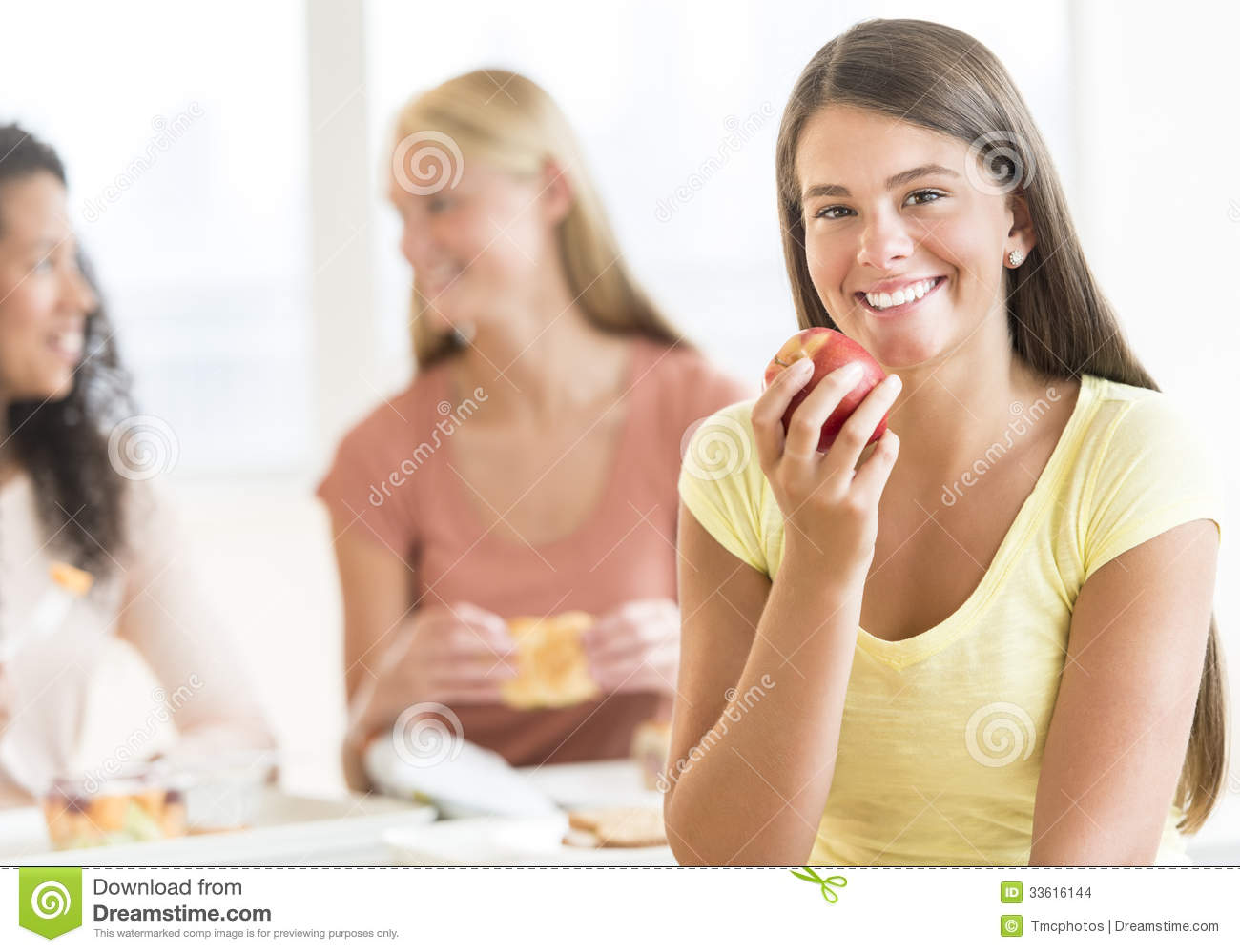 Teenage Student Eating Apple In University Canteen