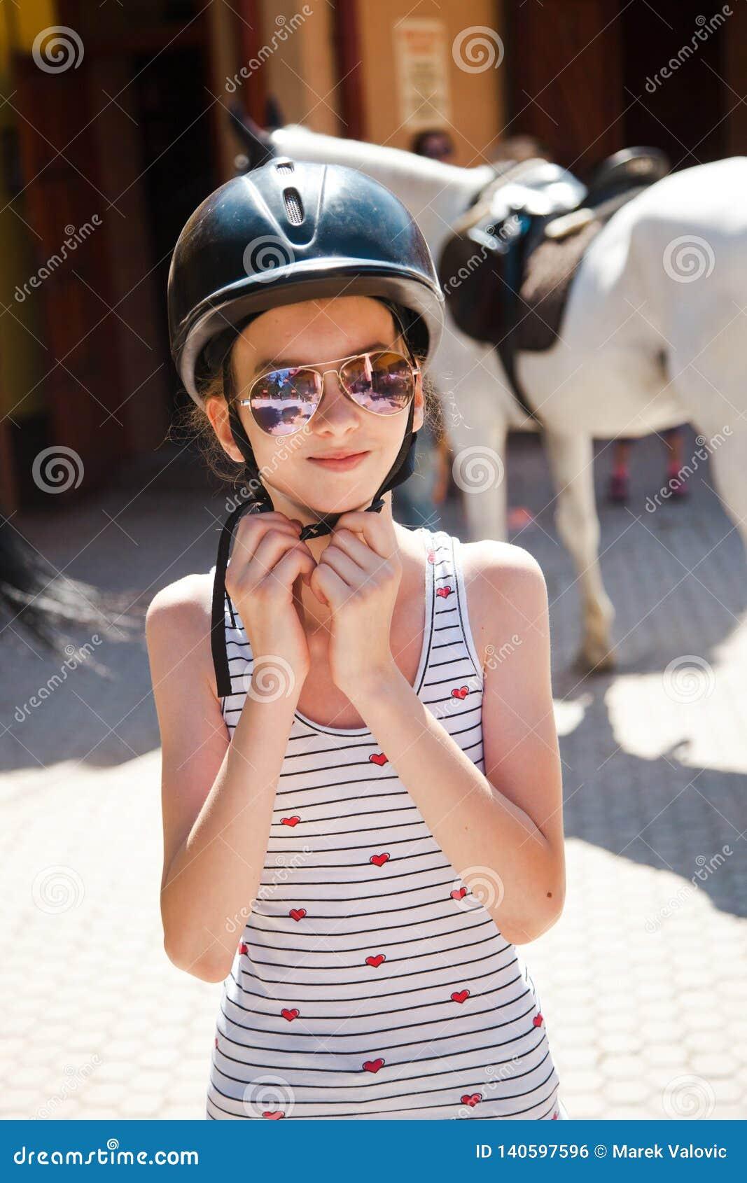 Teenaged dziewczyna jest ubranym jej hełm przed trenować