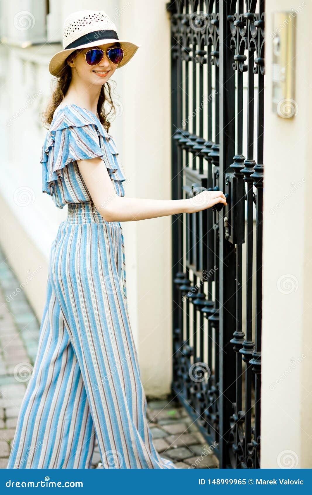 Teenaged dziewczyna w kombinezon sukni otwiera fałszować bramy