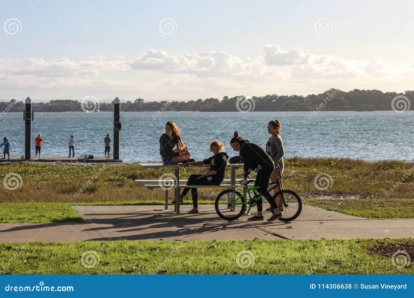 Teenaged dziewczyny przy pyknicznym stołem out wodą na opóźnionym Soboty popołudniu w Redlands Queensland Australia Maj 23 2015