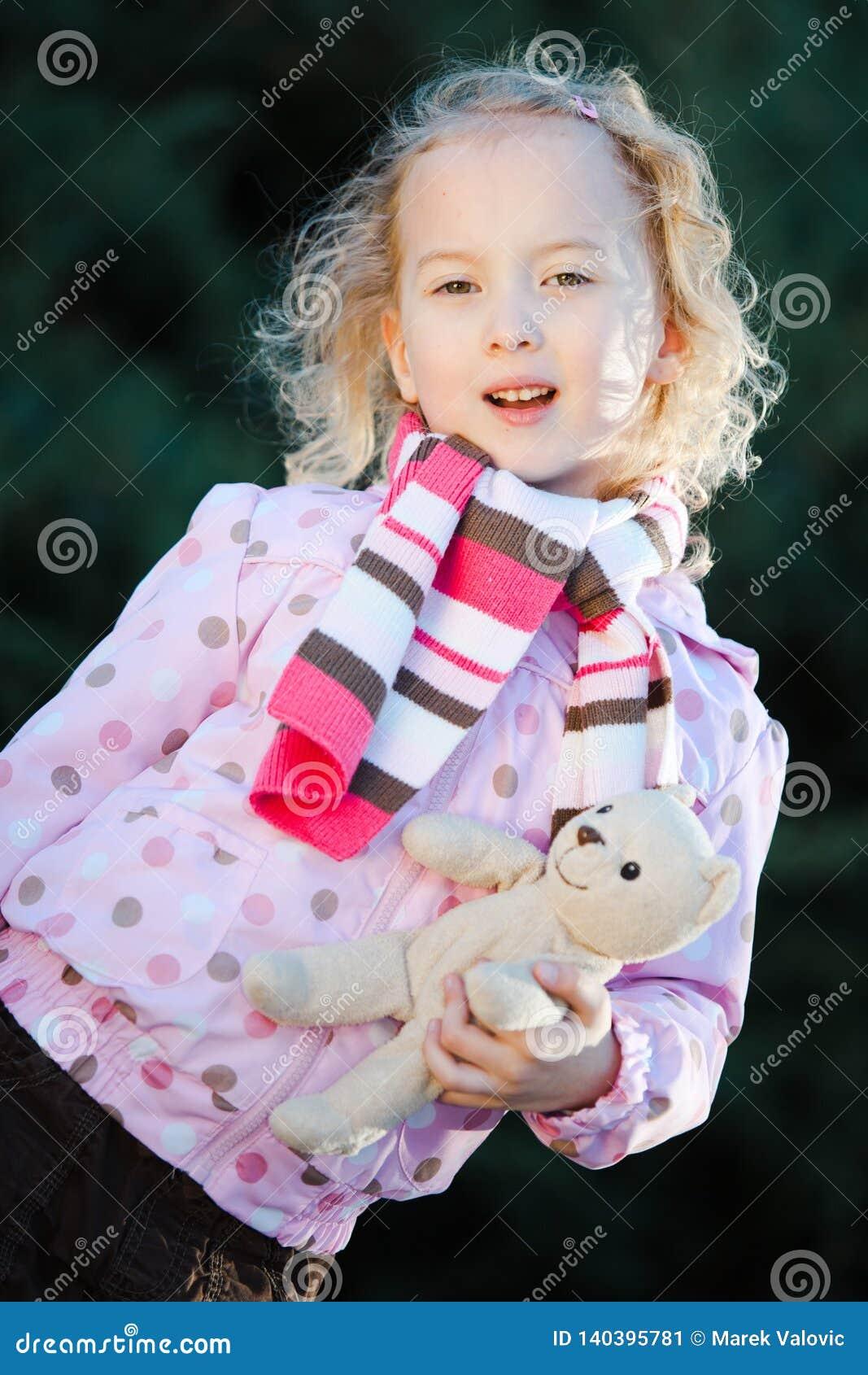 Teenaged girl posing with teddy bear- autumn time - dots purple jacket