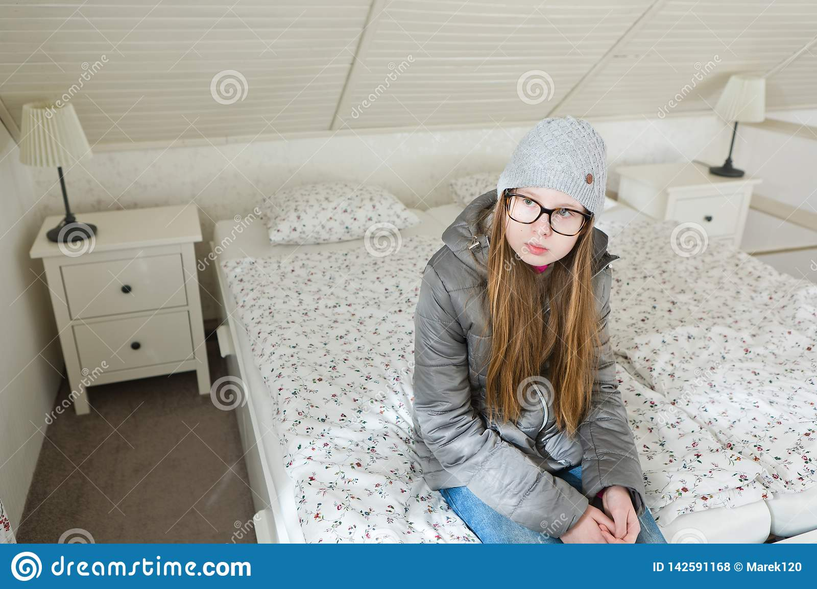 Teenaged girl sitting on bed morning before going to school - Lazy to start a working day - Mornings are difficult
