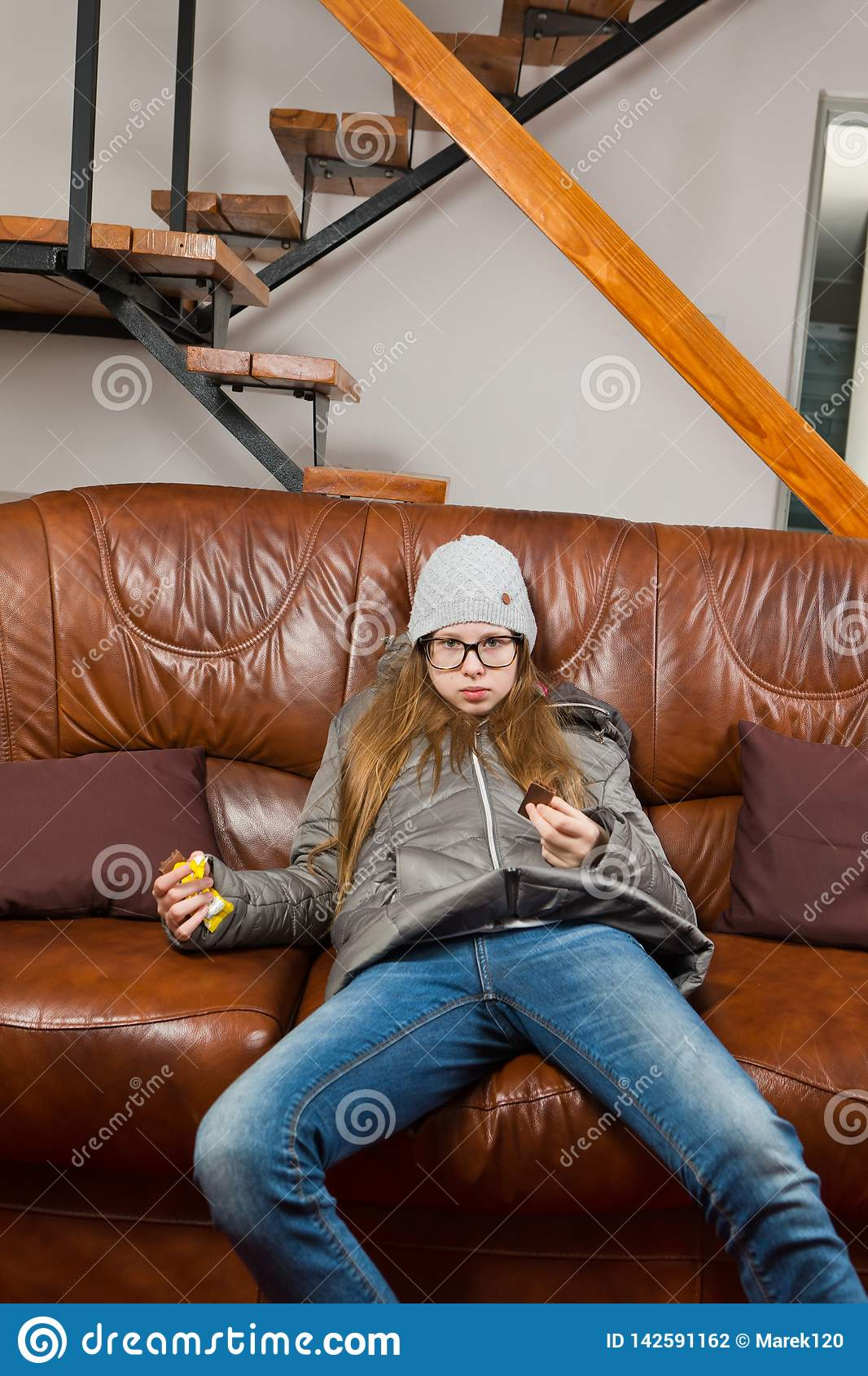 Teenaged girl sitting on sofa and eat chocolate - Lazy to do anything - Mornings are difficult