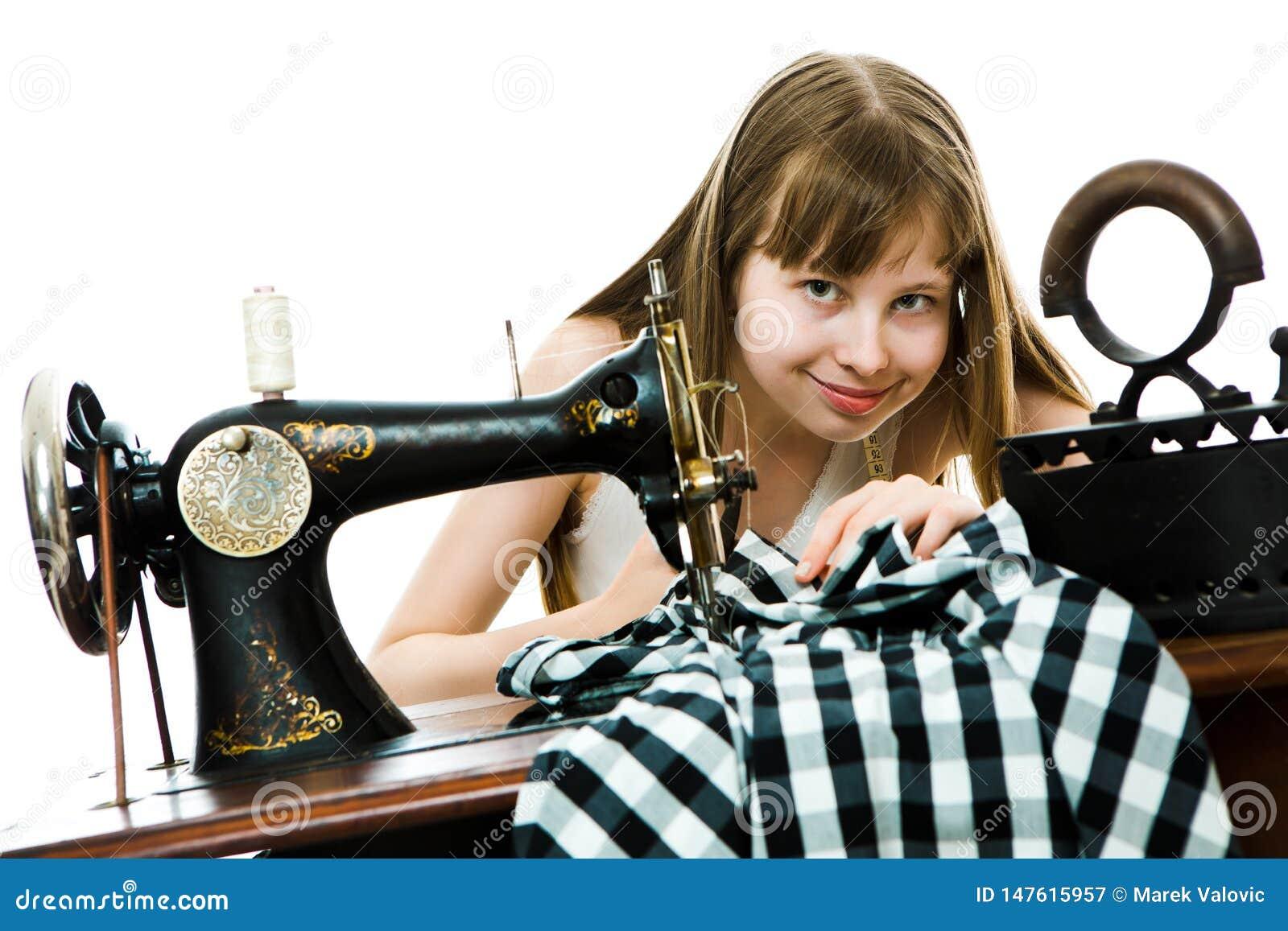 Teenaged Mädchen tailoress benutzen manuelle Sägemaschine, um ihr Kleid zu nähen