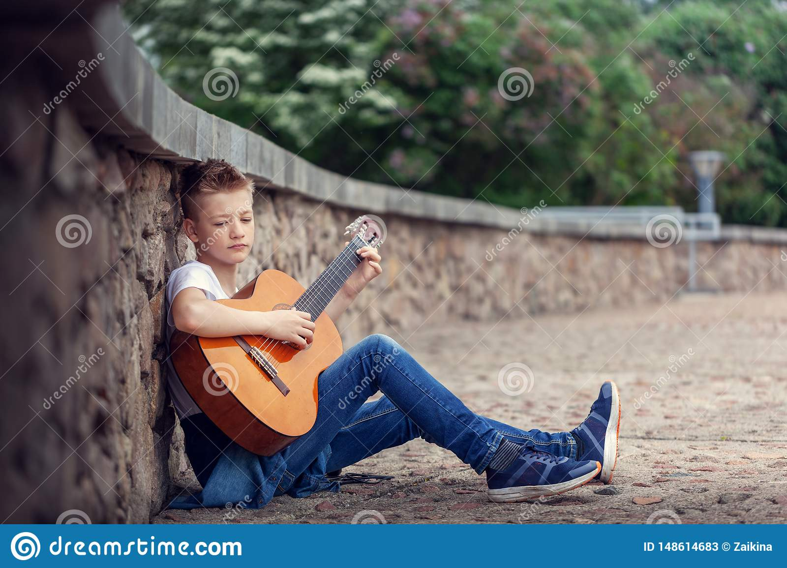 Teenager acoustic guitar playing sitting on the steps in the park
