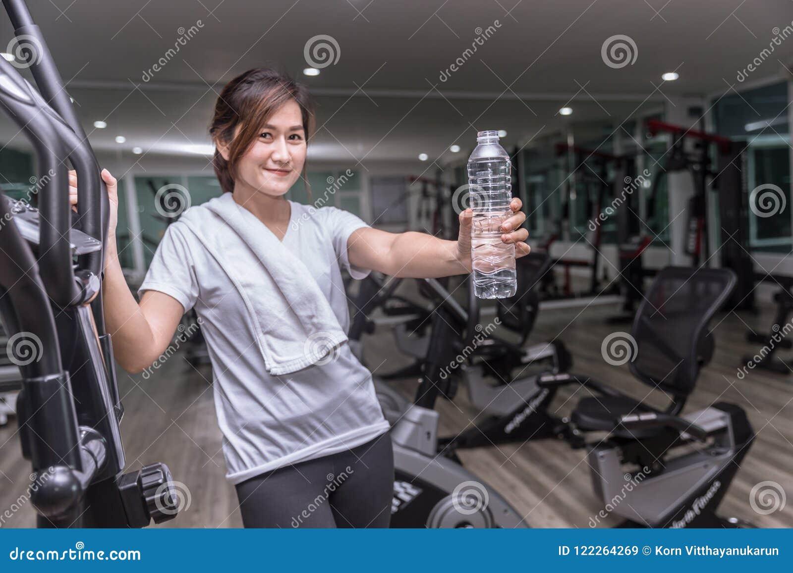 Teenager asiatico in acqua potabile della tenuta della mano di forma fisica