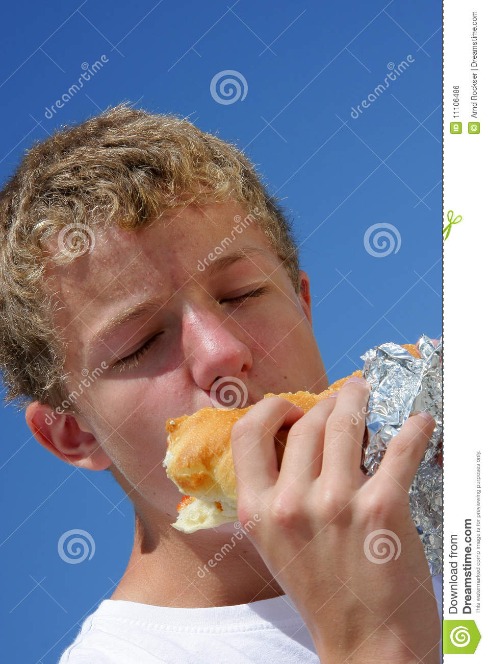 A Teenager Biting Into A Sandwich With Closed Eyes Royalty