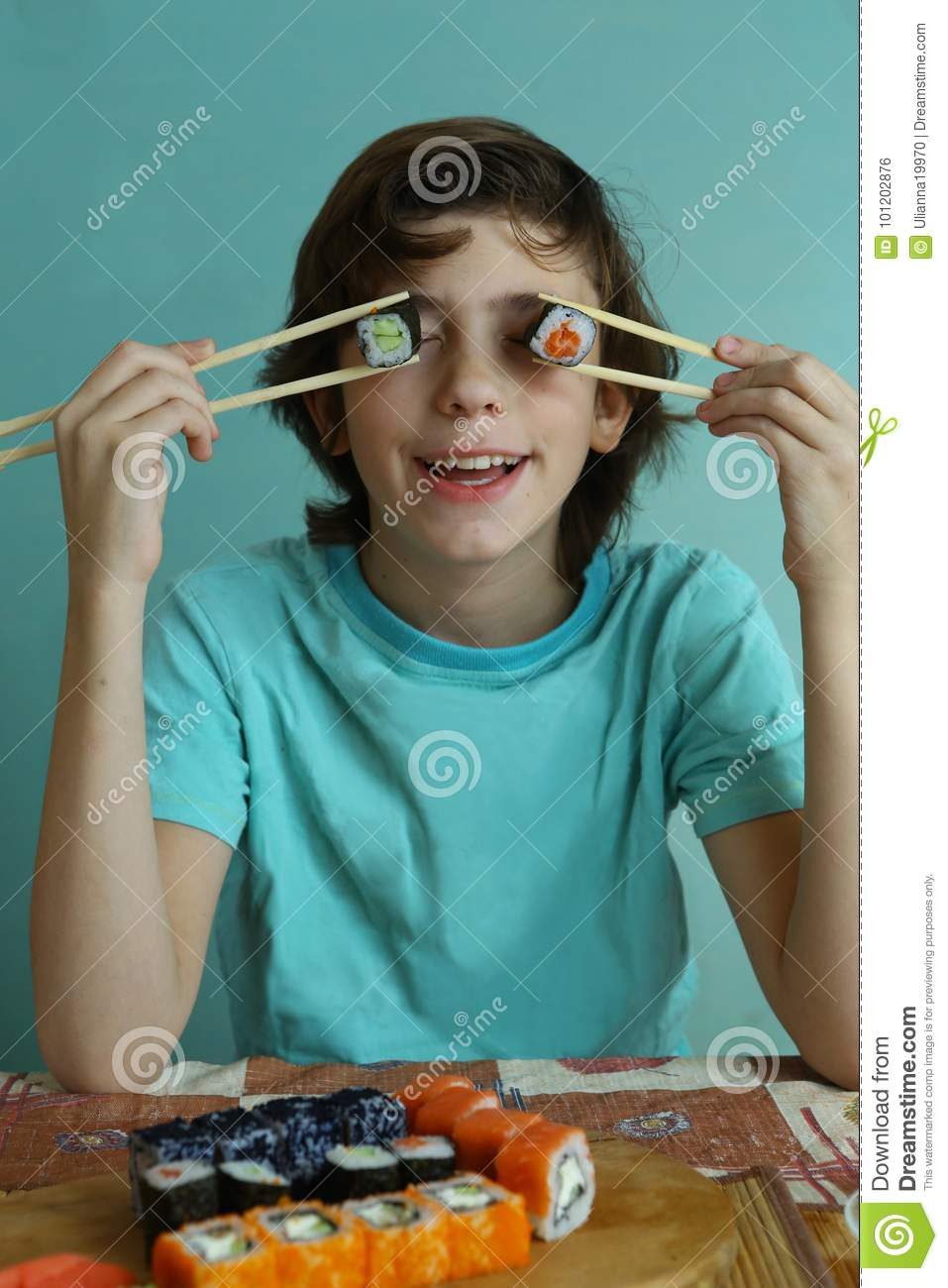 Teenager boy in blue shirt with sushi rolls make roll eyes for Blue fish sushi thai