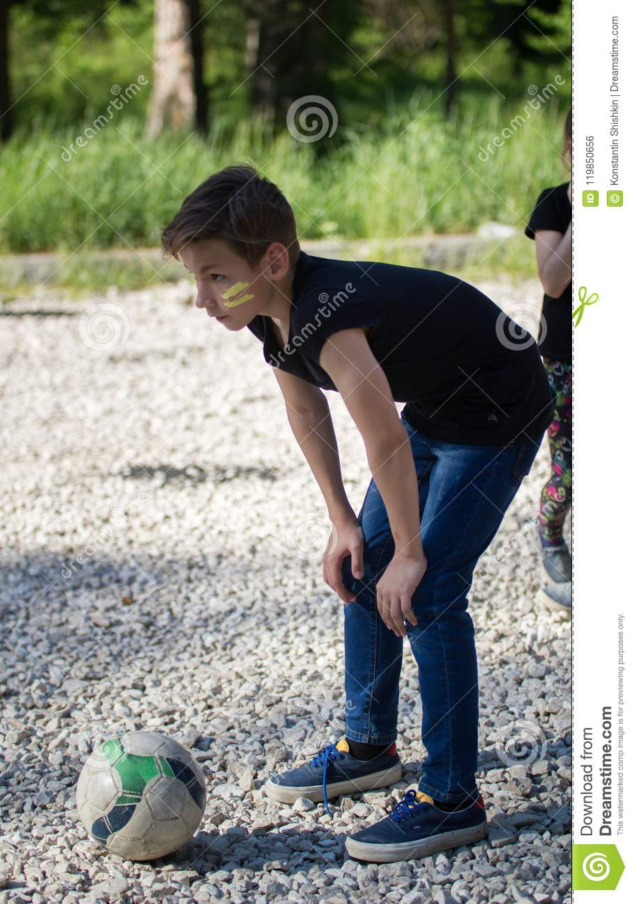 Teenager Boy Playing In Yard Football Preparing To Kick The