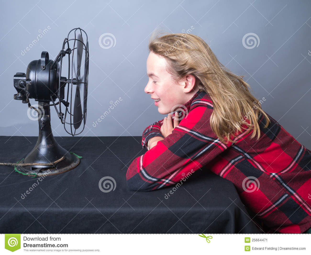 Cooling Off With Fan : Teenager cooling off in front of fan stock image