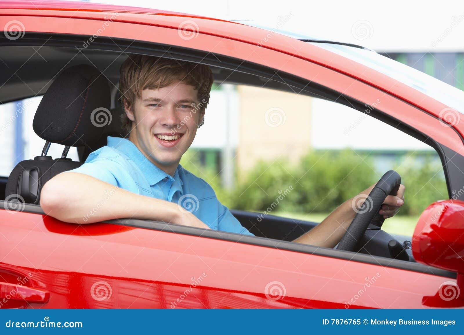 Teenager, der im Auto, lächelnd an der Kamera sitzt