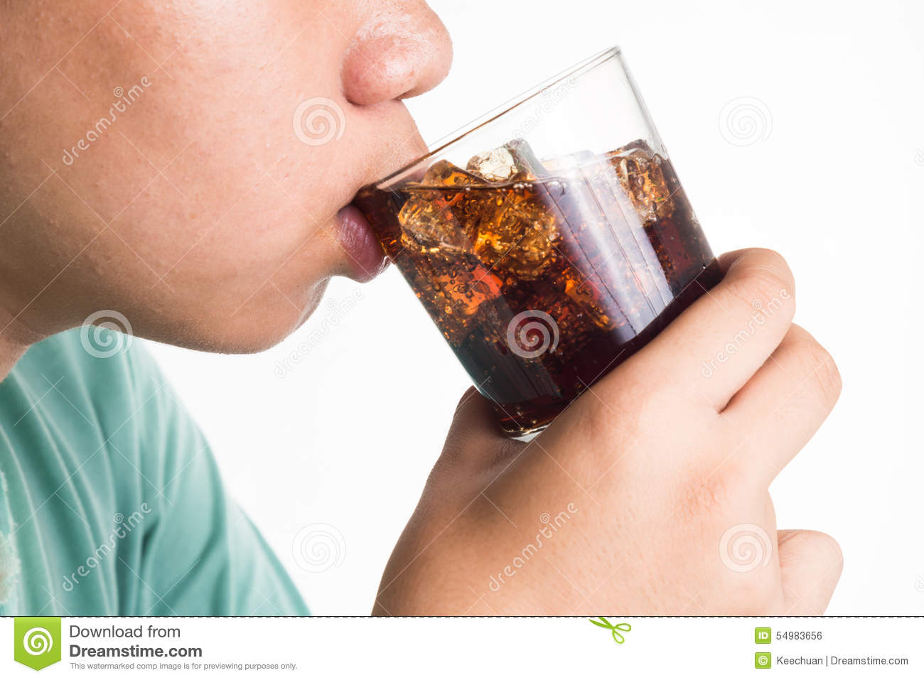 Teenager drinking a glass of refreshing cold fizzy cola drink