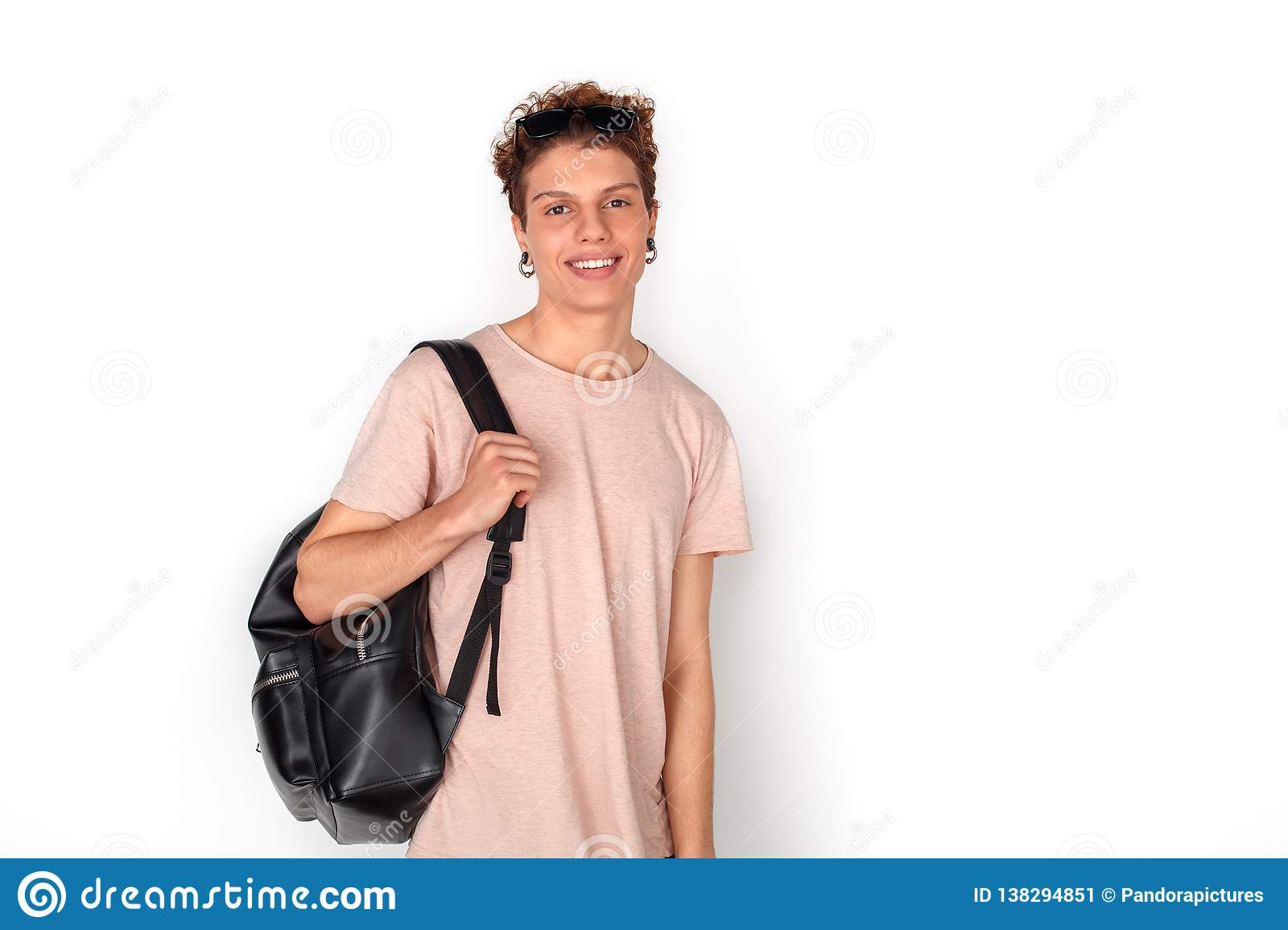 b62cdb404e404 Teenager With Earrings Carrying Backpack Studio Standing Isolated On ...