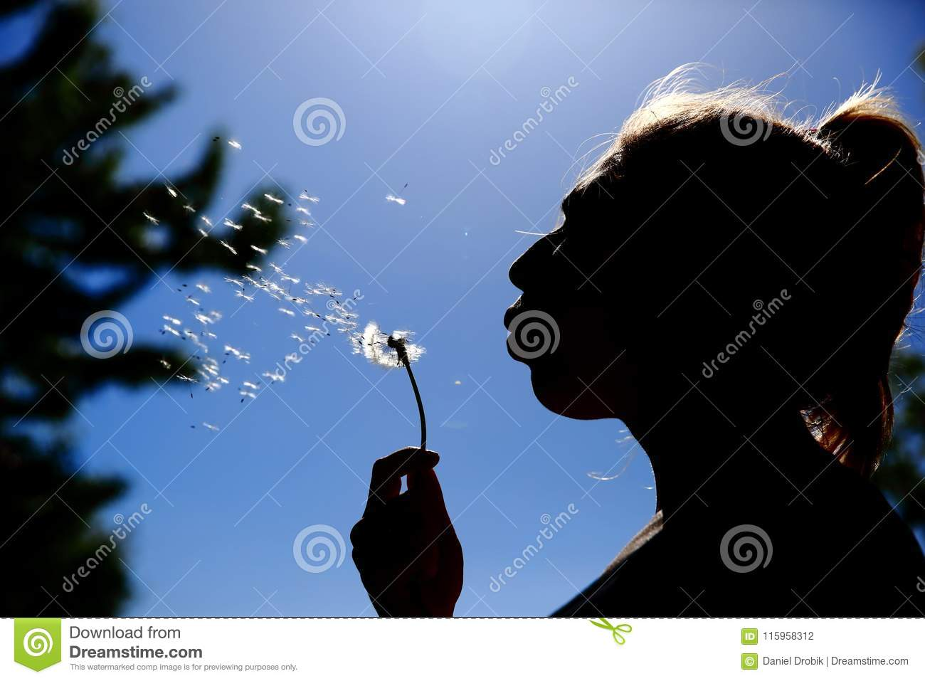 The teenager gently blows and spreads the dandelion seeds against the blue sky.