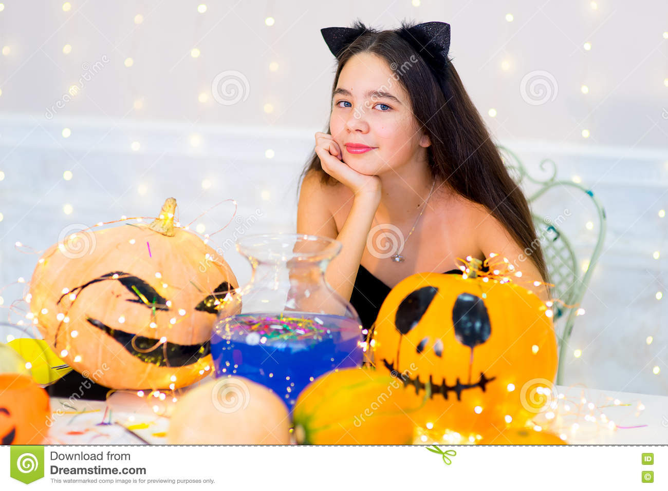 Teenager Girl In Cat Costume Posing With Pumpkins Stock Photo