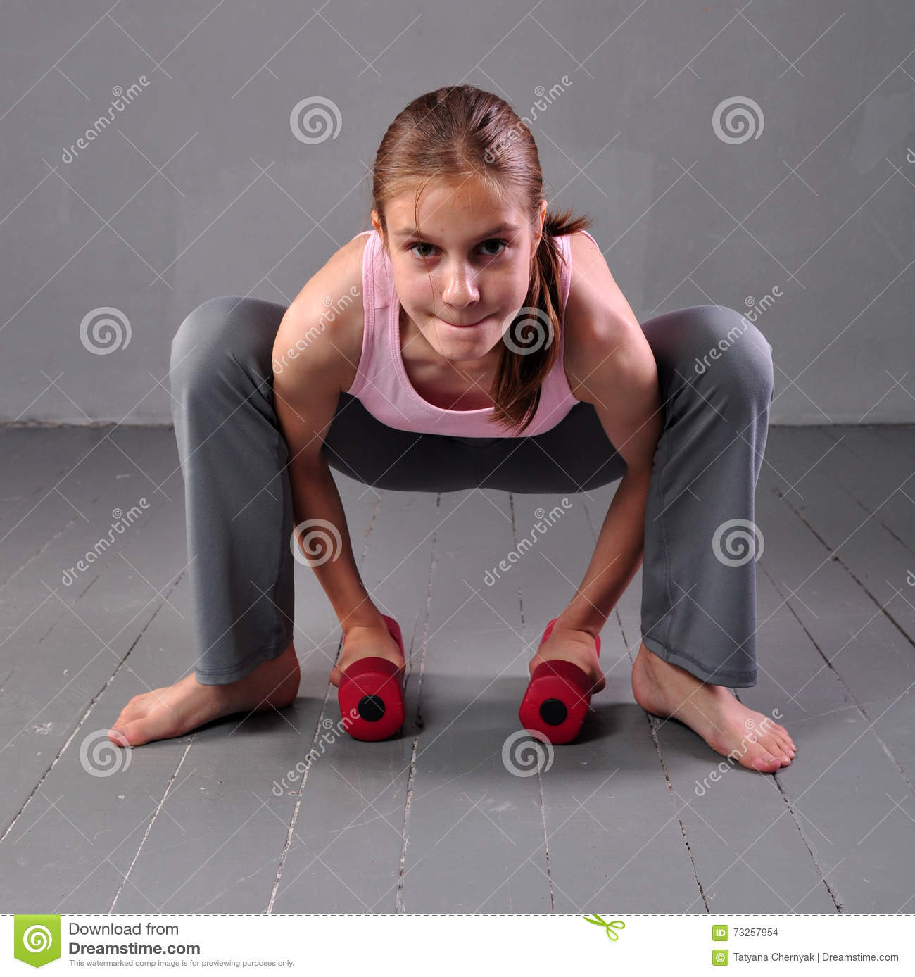Teenager girl doing exercises with dumbbells to develop with dumbbells  muscles on grey background. Full