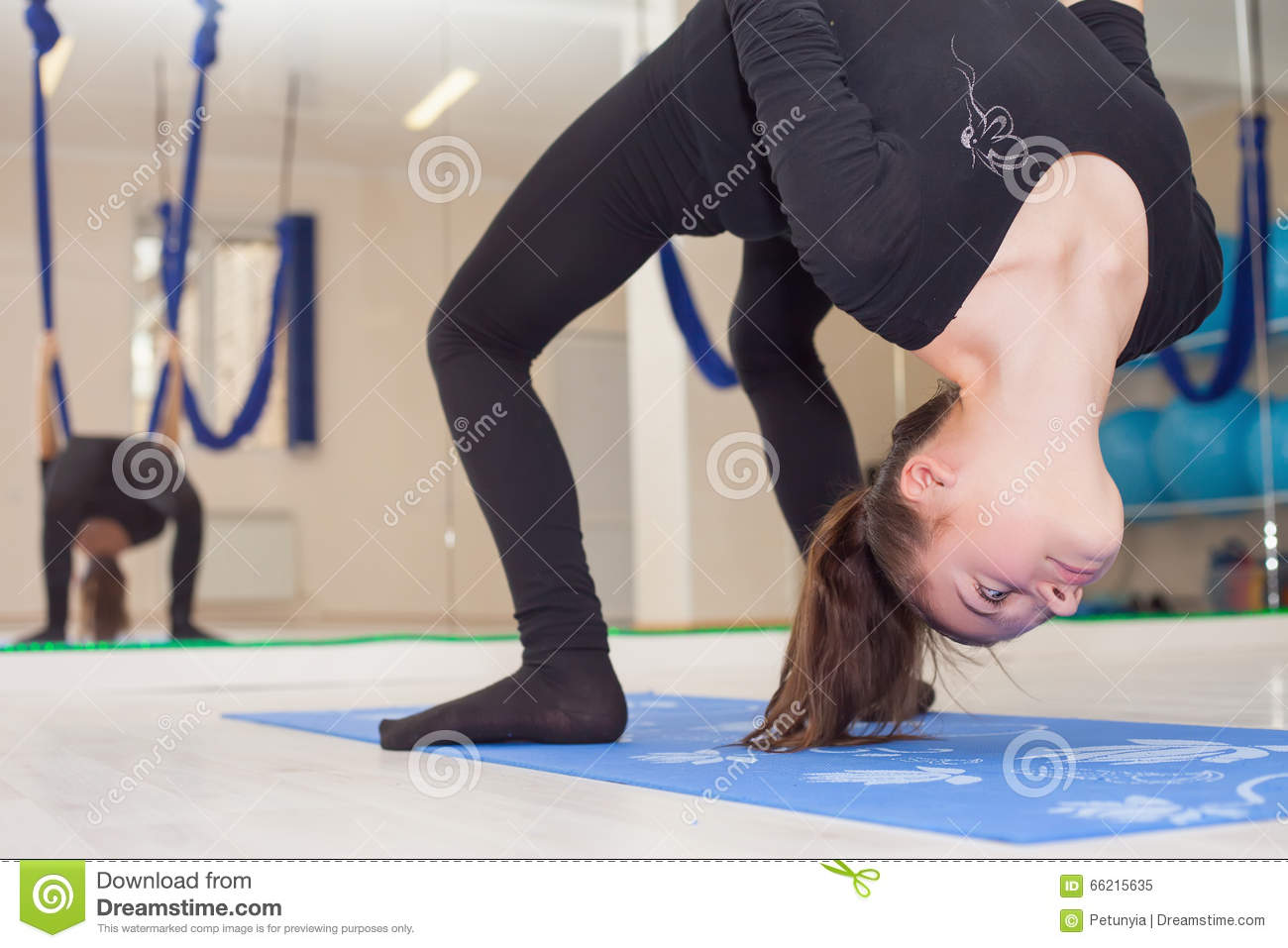 Teenager girl doing stretching and twine, aerial yoga