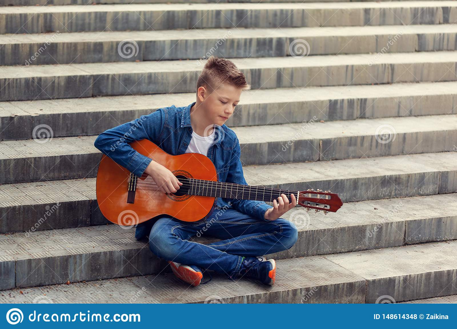 Teenager guitar playing sitting on the steps in the park