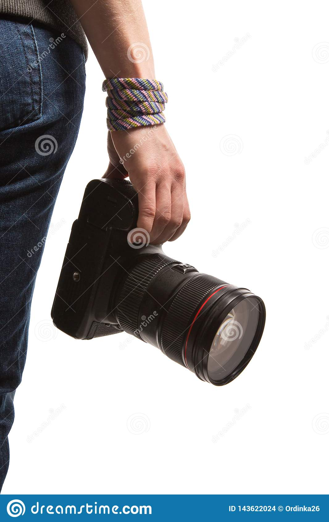 A teenager holds in her hand a DSLR camera. Isolated on white background