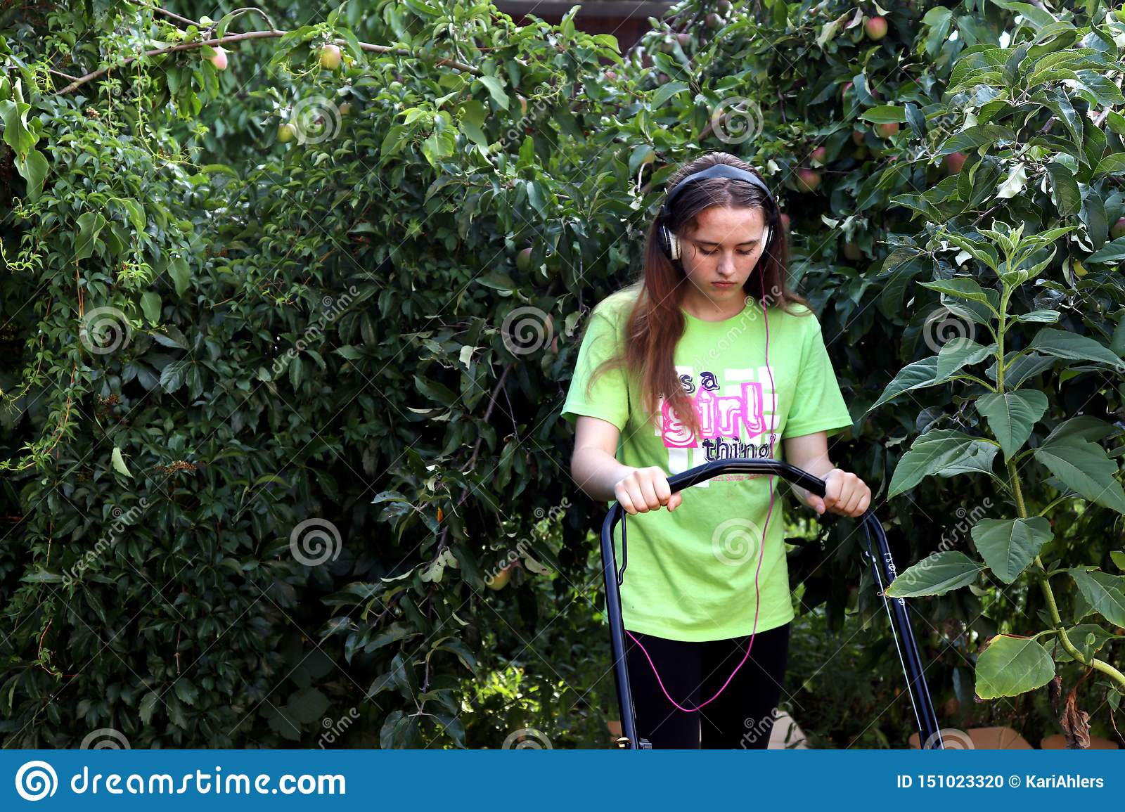 Teenager mowing lawn surrounded by apple tree
